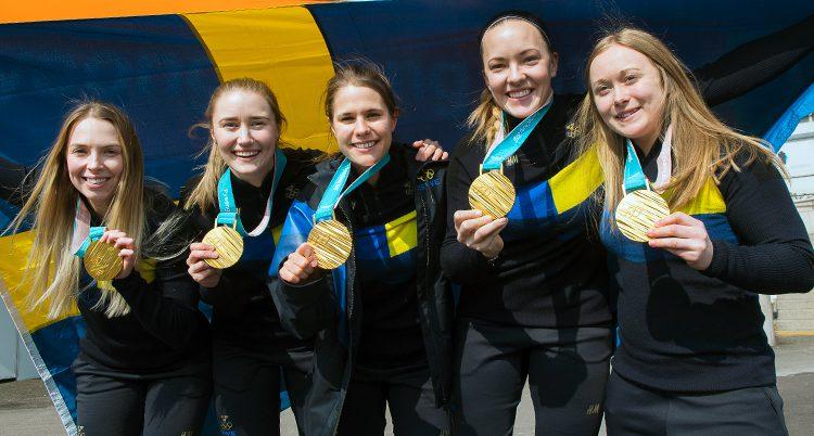 Laget håller upp sina guldmedaljer från OS.