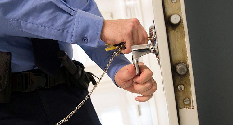 En närbild på en polis som låser en dörr.