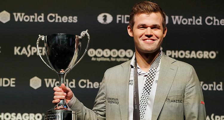 Magnus Carlsen håller i bucklan han vann.