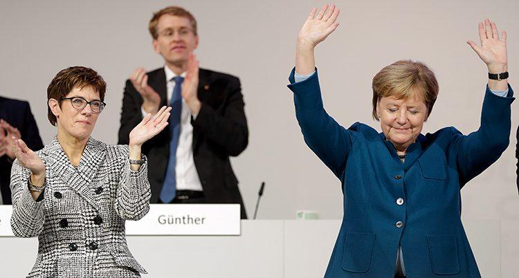 Merkel lyfter händerna och vinkar till publiken. Annegret Kramp-Karrenbauer står bredvid och applåderar.