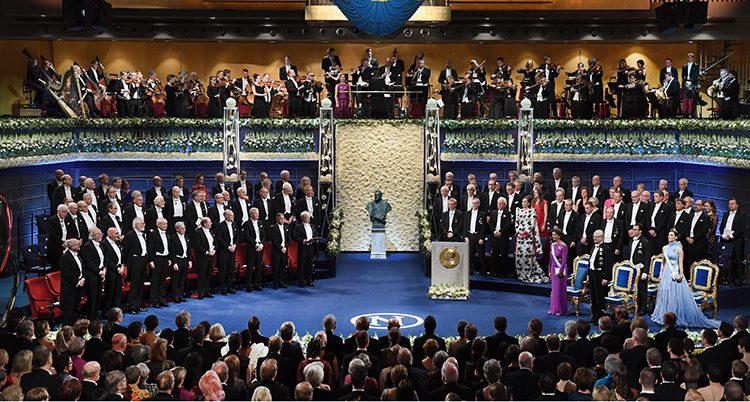 En bild från Konserthuset och förra årets prisutdelning. Vi ser hela scenen ovanifrån, nobelpristagarna i stolar till vänster, kungafamiljen till höger. i mitten står en byst av alfred nobel.
