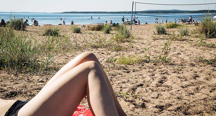 En kvinna solar på en strand.
