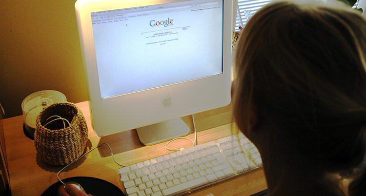 En kvinna sitter vid en dator.