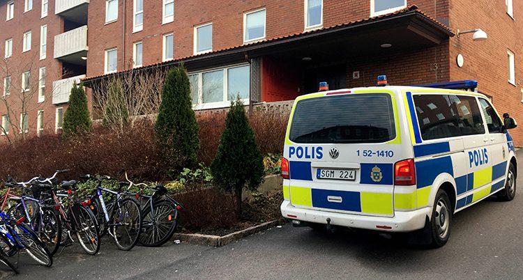 En polisbil utanför ett lägenhetshus.