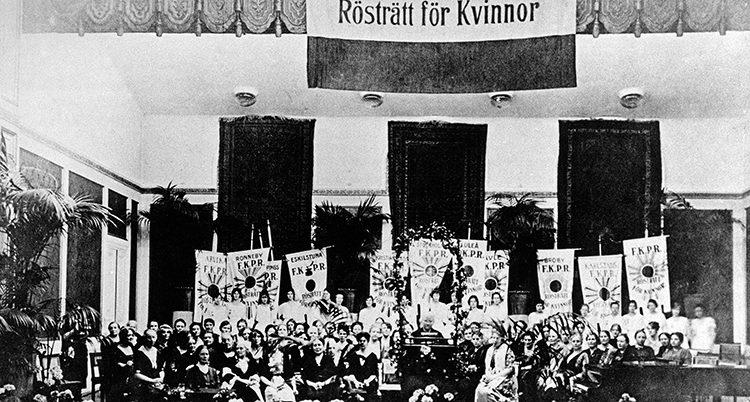 En svartvit bild tagen på avstånd. En stor grupp kvinnor med plakat i en stor sal. Överst syns en banderoll där det står Rösträtt för kvinnor.
