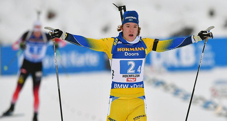 Svenska Sebastian Samulelsson i gul dräkt åker i mål med armarna utsträckta.