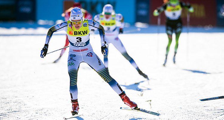Stina Nilsson i vit dräkt på sina skidor.