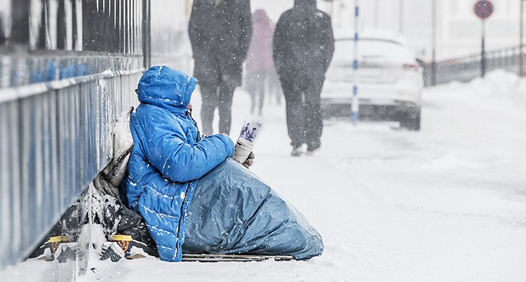 En tiggare sitter på en gata full med snö.