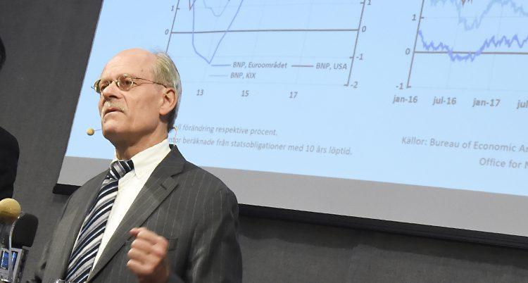 Stefan Ingves framför en bild med tabeller