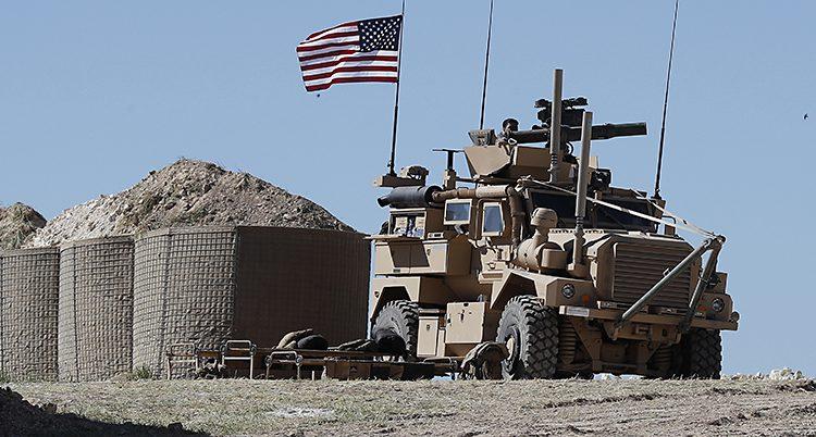 En jeep med en kanon ocn en amerikansk flagga