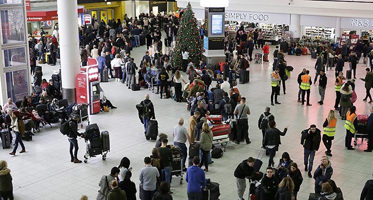 En stor hall i Gatwick full av folk som köar fotad ovanifrån. En julgran finns också mitt i bilden.