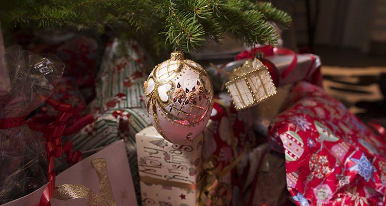 En bild på en del av en julgran. Vi ser en gren med en rosa förgylld julgranskula och några inslagna julklappar under.