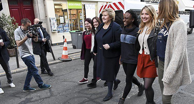 Skådespelarna går på en gata och hoåller om varandra och ler tillsammans med Erna Solberg.