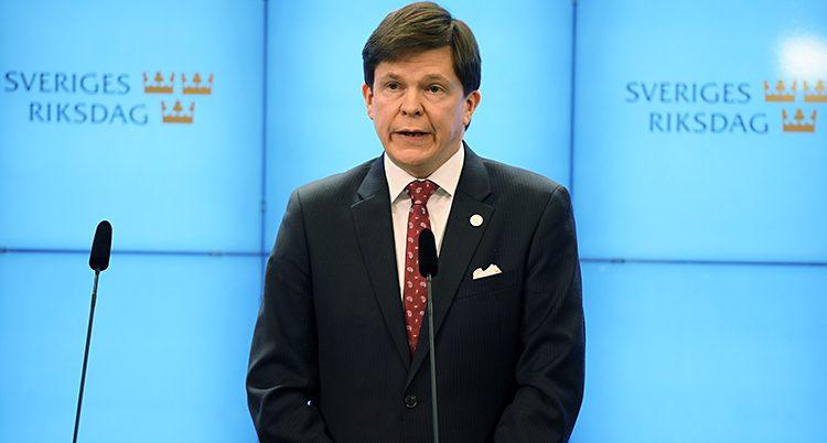 Talmannen framför en vägg där det står Sveriges Riksdag.