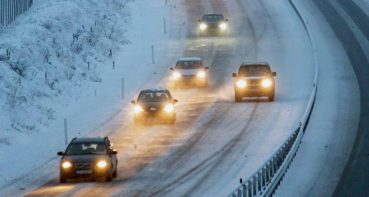 Bilar på en snöig väg.