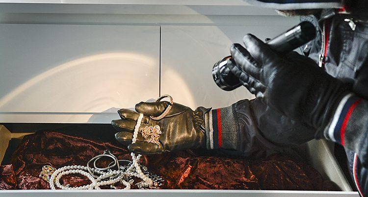 Två handskbeklädda händer. En håller smycken, den andra lyser på dem med en ficklampa.
