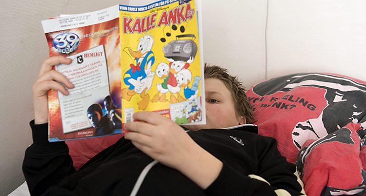 En pojke läser Kalle Anka.
