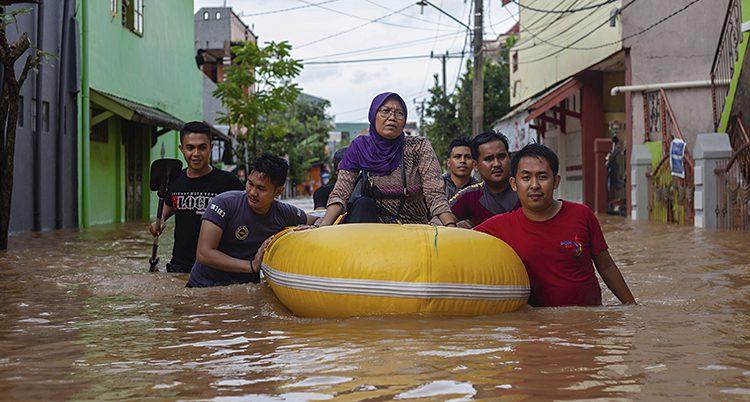 Folk på en gata som svämmats över.