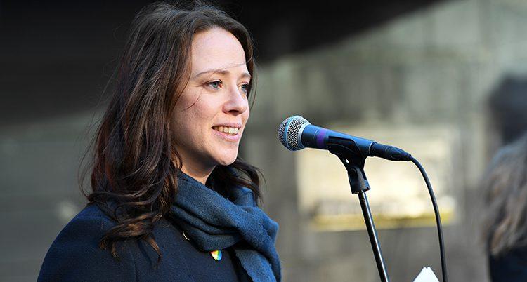 Åsa Lindhagen ler framför en mikrofon.