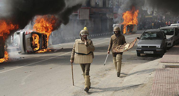 Soldater går på en gata med brinnande tunnor