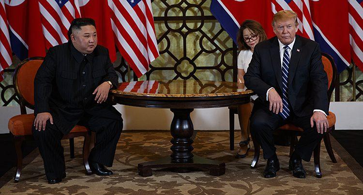 Kim och Trump sitter vid varsitt bord och ser sura ut.