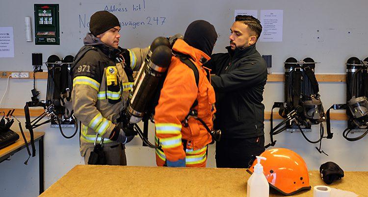 En elev får hjälp med utrustningen av två av brandmännen.