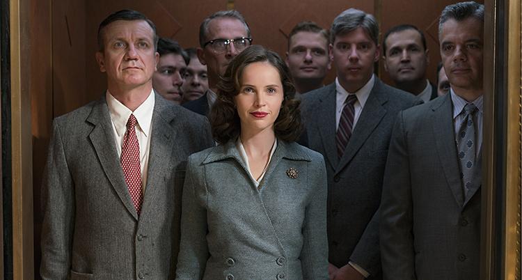 Skådespelaren Felicity Jones i filmen om Ruth Bader Ginsburg. Hon står omgiven av män.