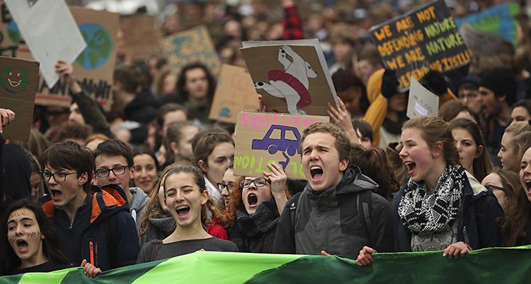 Massor av unga trängs under en demonstration. De håller plakat och ropar slagord. I Belgien.