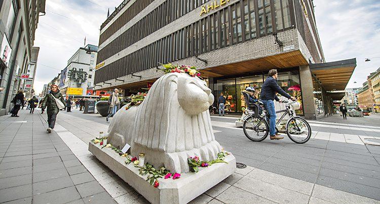 Ett lejon av sten med blommor omkring