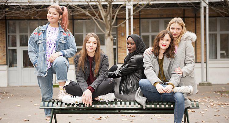 Fyra unga tjejer vid en bänk på en skolgård