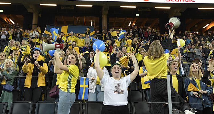 Bild på publiken i gula tröjor som hejar och skrattar.
