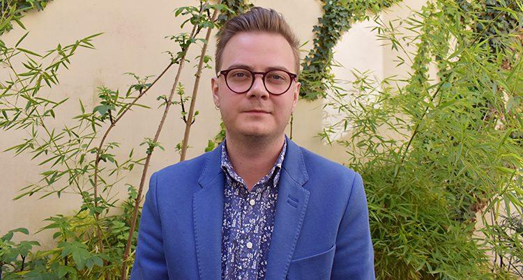 En ung man i blå kavaj med glasögon står framför en vägg med växter
