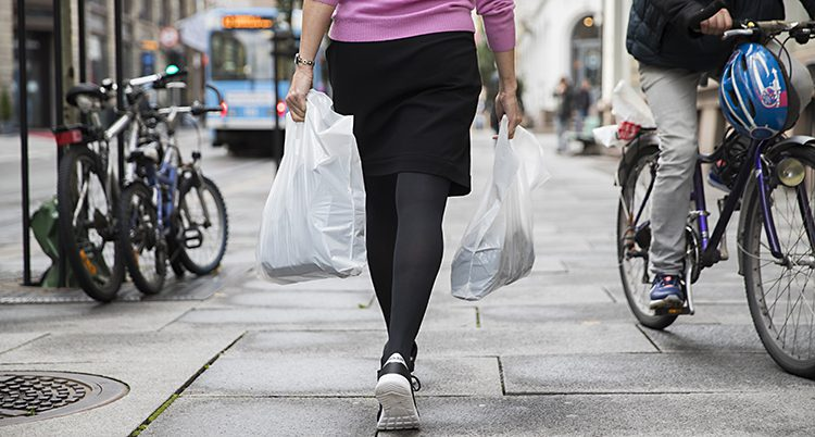 En kvinna med plastkassar.