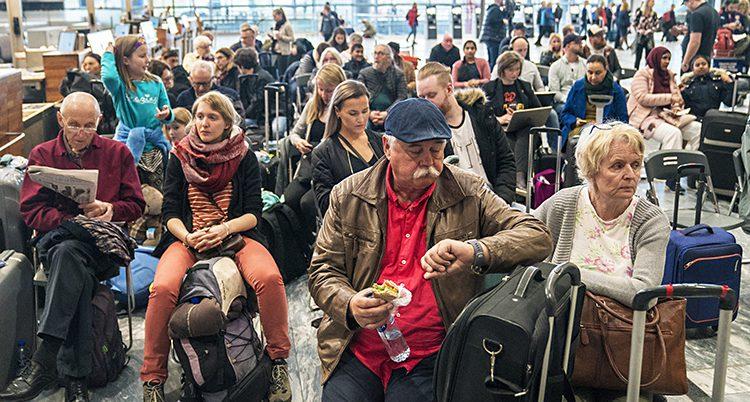 Människor sitter och väntar på flygplatsen.