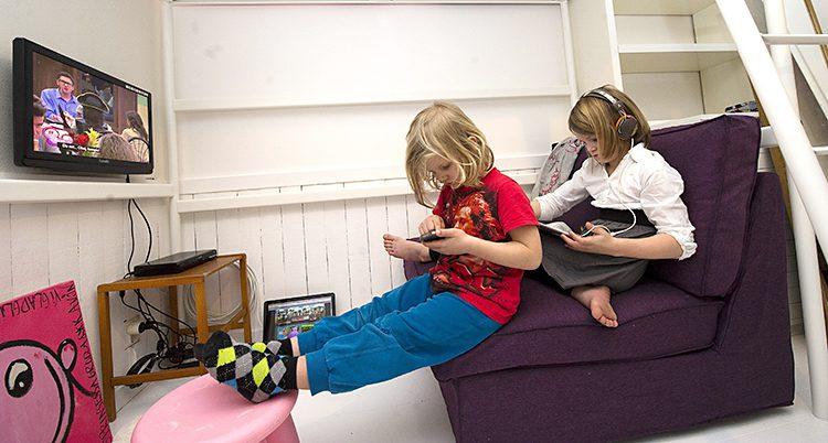 Två barn sitter i en soffa med mobiltelefon och surfplatta.