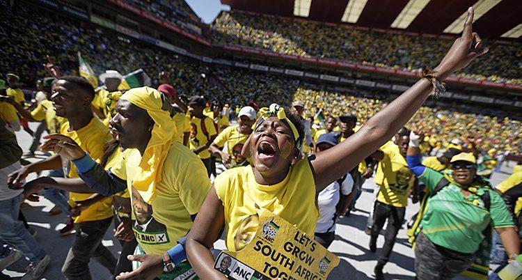 Massor av människor i gula kläder skriker och hurrar