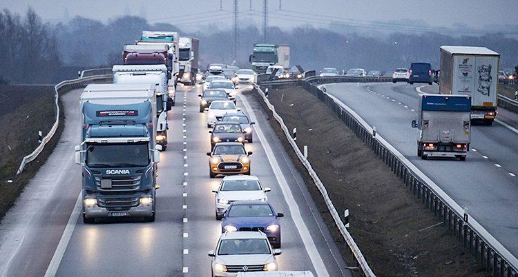 En kö med bilar och lastbilar på motorvägen