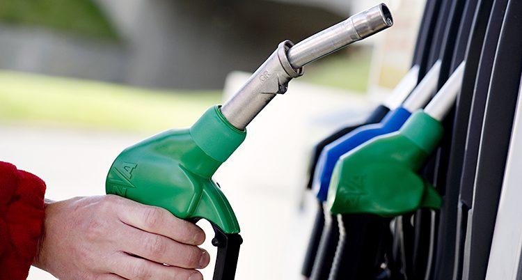 En hand sträcker sig mot en bensinpump