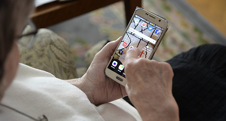 En äldre kvinna surfar på en mobiltelefon.