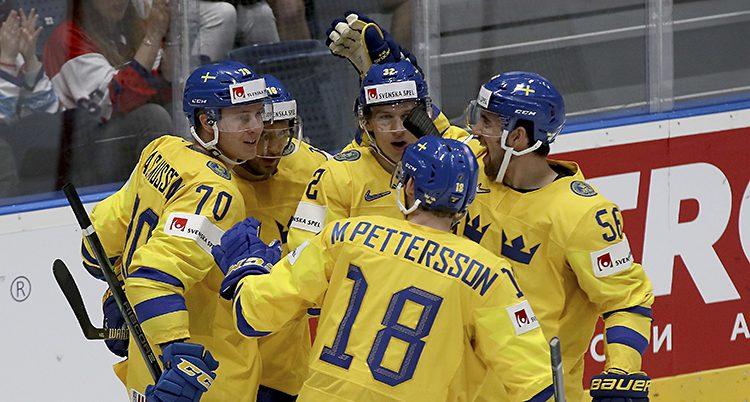 Spelare i Tre Kronor kramar om varandra på isen.