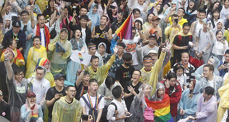 Folk i Taiwan står utomhus på en gata och jublar.