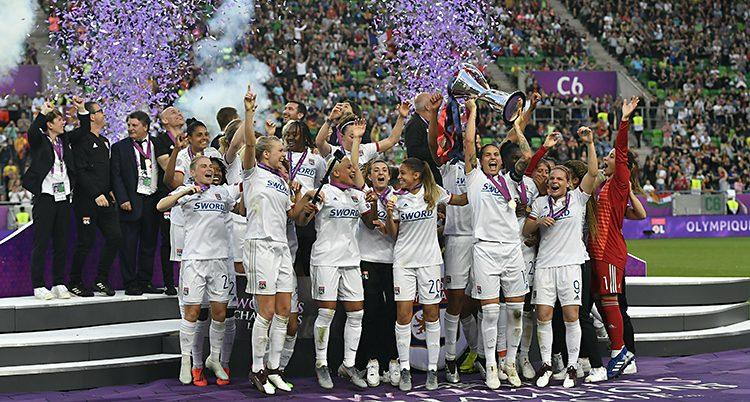 Lyon firar segern på planen. De sträcker armarna i luften. Bakom sprutar lila konfetti.