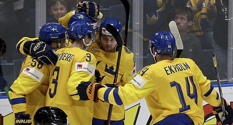 En bild på flera spelare i gult som kramas.