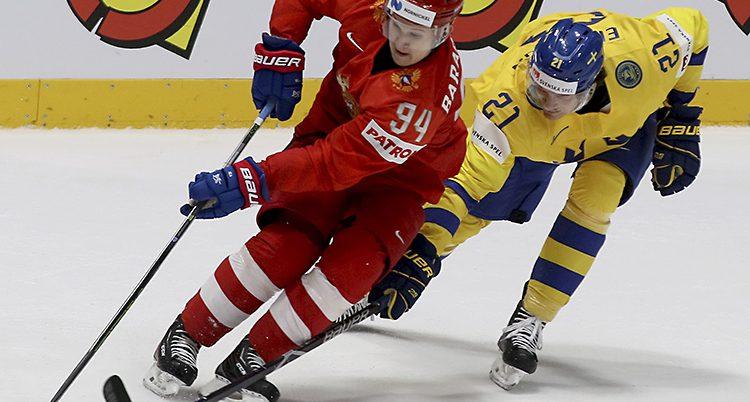 En svensk spelare och en rysk spelar kämpar om pucken i ishockey.