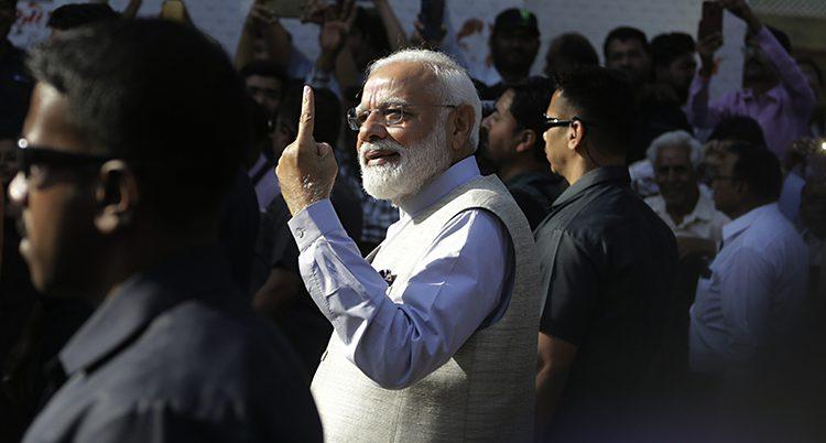Narendra Modi efter att han röstat. Han sticker upp ett finger i luften för att visa bläcket man får på fingret efter att ha röstat.