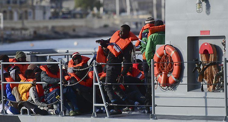 Flera personer i röda flytvästar i en stor båt.
