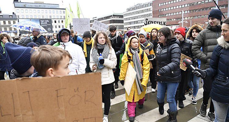 Greta och flera andra i regnkläder följs av journalister.