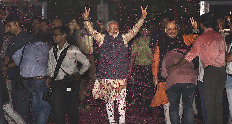 Narendra Modi sträcker händerna i luften. Röda blad faller runtomkring.