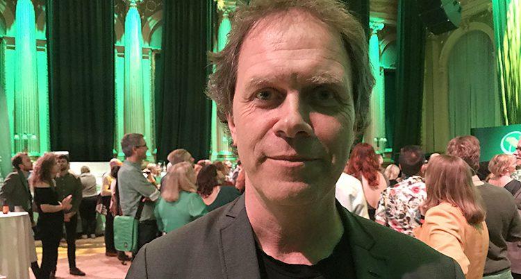 Pär Holmgren står i en stor lokal med flera människor i bakgrunden.
