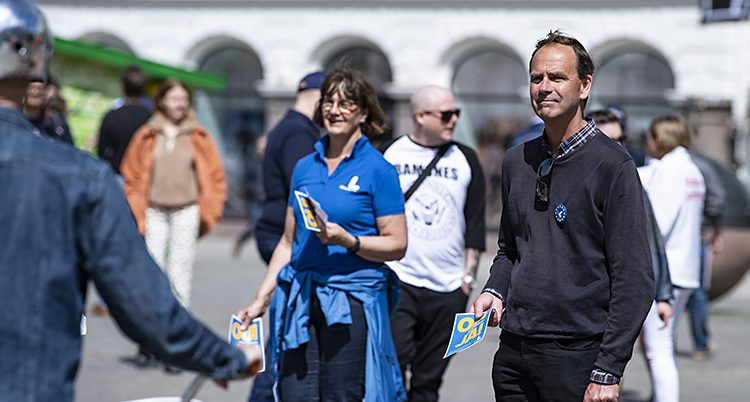 En kvinna och en man delar ut reklam för Liberalerna.